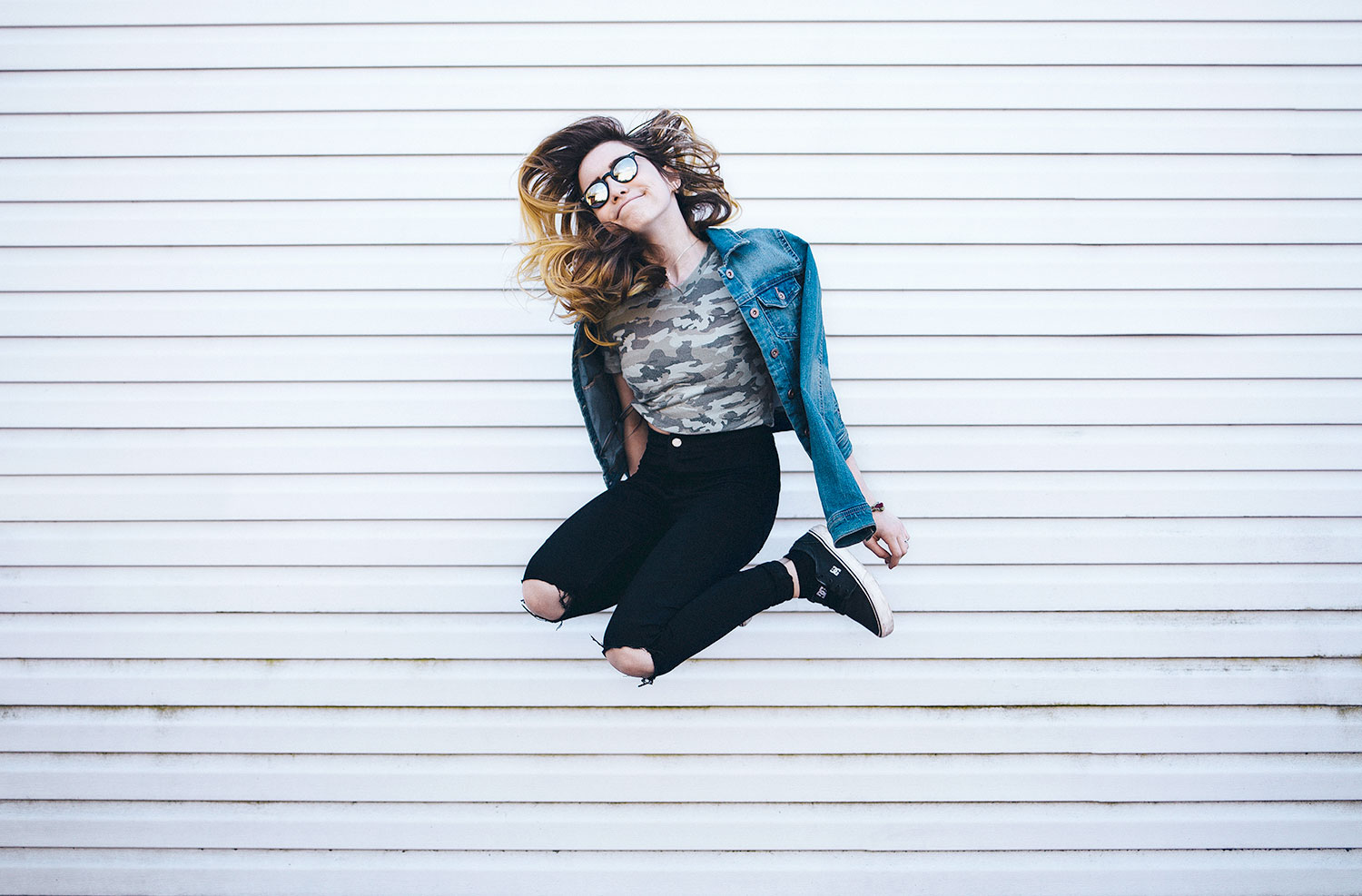 Woman jumping in front of wall.