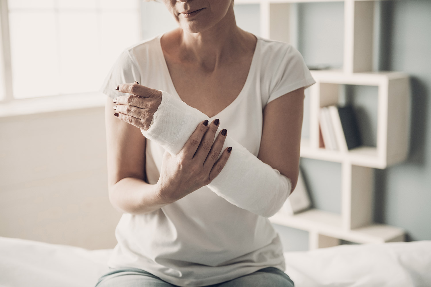 Woman holding her broken arm with cast
