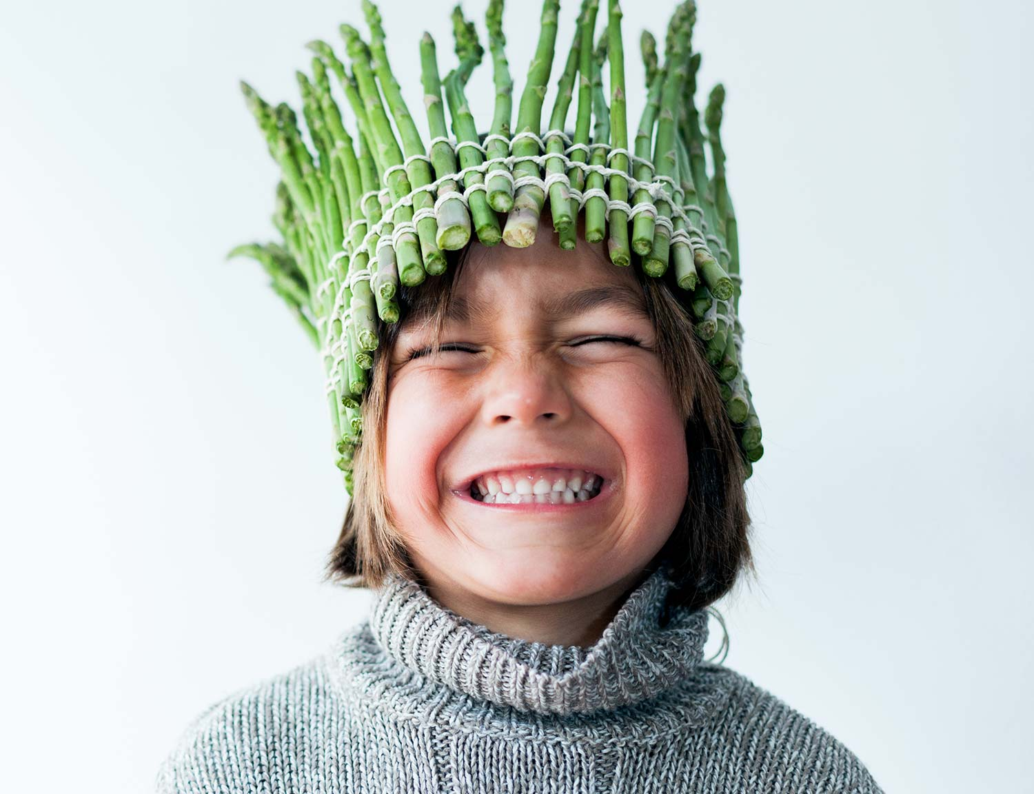 Young child wearing a crown made of asparagus