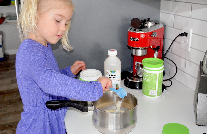 Little girl putting gelatin into a pot